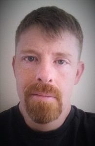 Author Justin Edison, looking unimpressed with his reddish goatee.